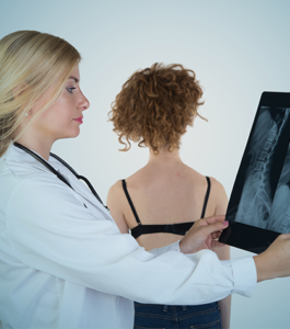doctor examines x-ray of adolescent spine with spinal deformity