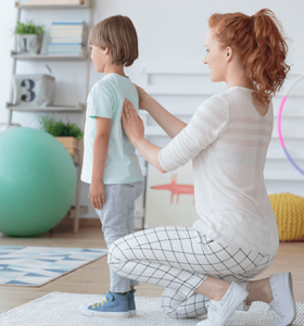 physical therapist with child who has spinal deformity