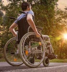 man in wheelchair with sunset